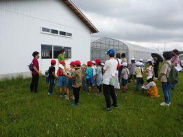 【写真】クラブハウス前で小学2年生の生徒さん達を前にいちごの話をする農園主